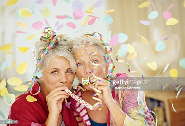 two senior women playing with party toys in living room, portrait - party blower stock pictures, royalty-free photos & images