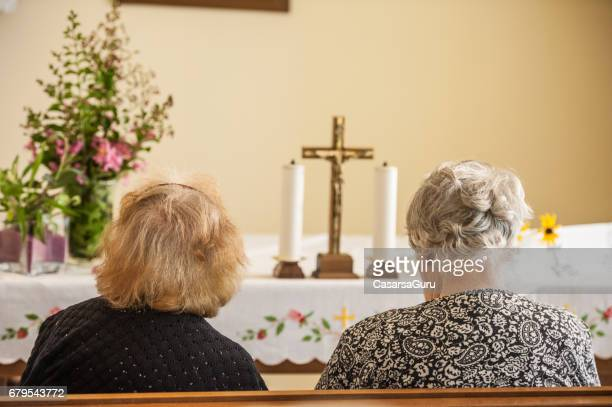 Two Senior Women Praying In The Chapel Of The Retirement Community
