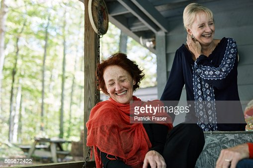 Two senior women sit on cabin porch in woods and laugh