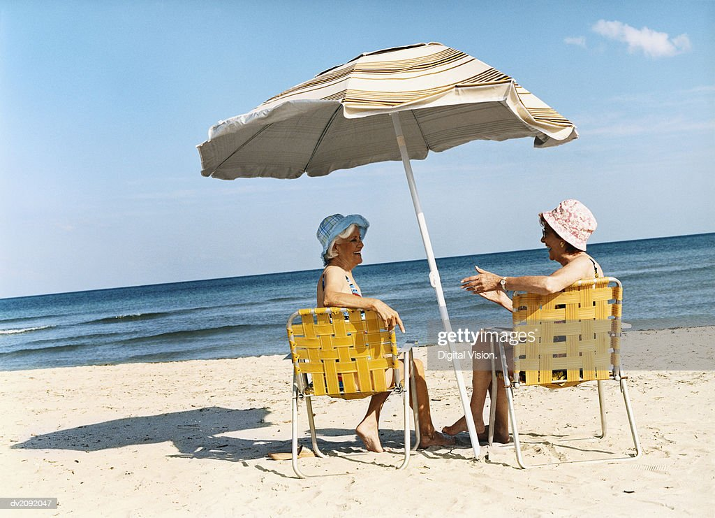 Two Senior Women Sit on Deckchairs Under a Parasol on the Beach, Talking : Stock Photo