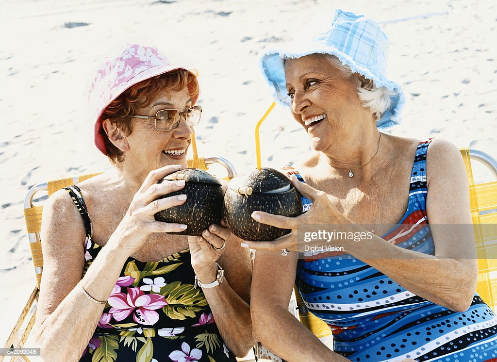 Two Senior Women Sit on the Beach Making a Toast With Coconut Cocktails : Stock Photo