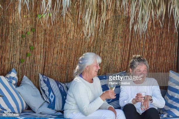 Two Senior Women sitting in pool cabana