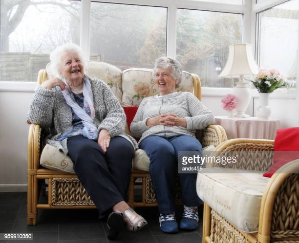 two senior women sitting in sun room /conservatory