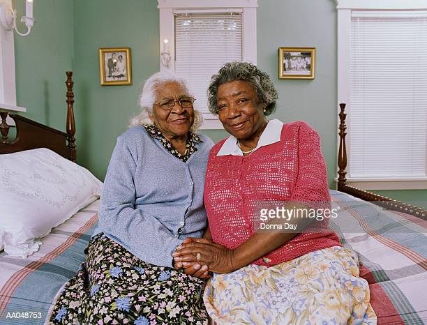 Two senior women sitting on bed, portrait