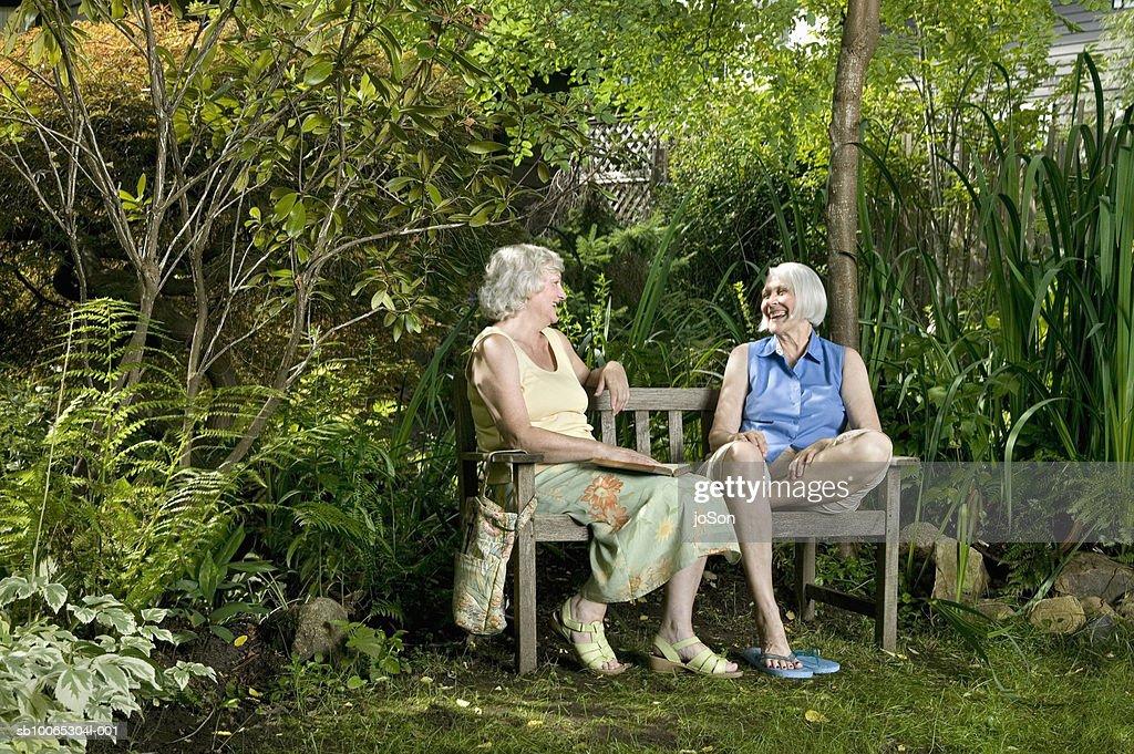 Two senior women sitting on garden bench talking : Foto stock
