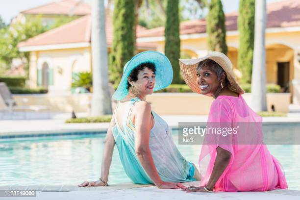 two senior women sitting on pool deck, feet in water - wide brim stock pictures, royalty-free photos & images