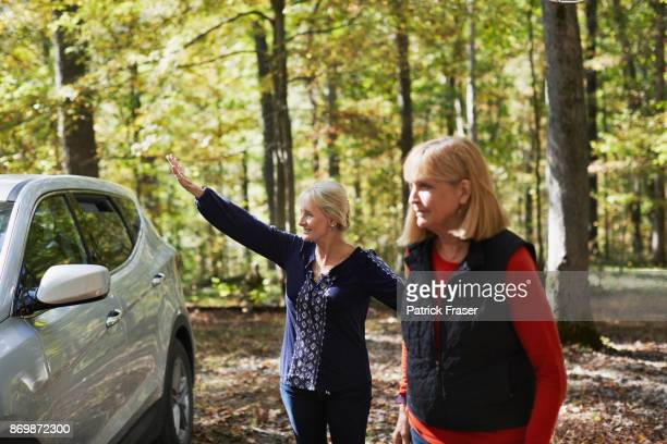 two senior women stand outside by car in woods as one waves - bloomington indiana stock photos and pictures