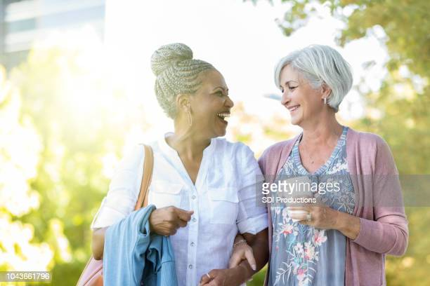 two senior women walk outdoors together - diversity and inclusion stock pictures, royalty-free photos & images