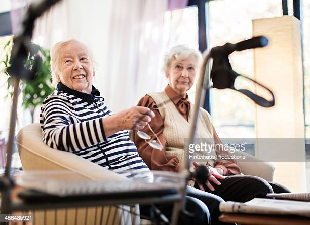 two senior women with wheeled walker - altersheim stock-fotos und bilder