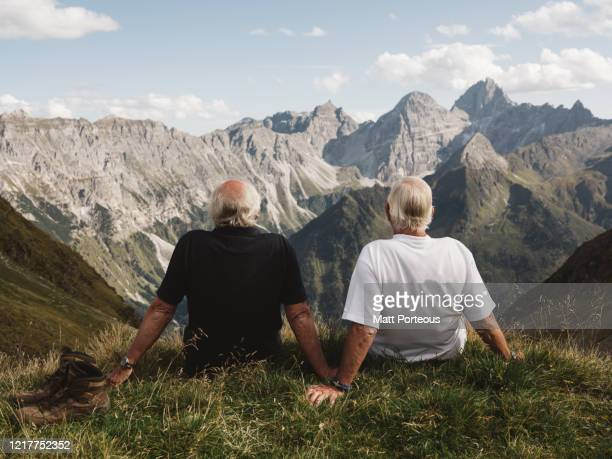 two seniors hikers sit and admire the view - pensionierung stock-fotos und bilder