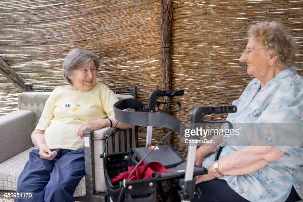 two seniors women relaxing in the shade at the nursery home - residential care stock photos and pictures