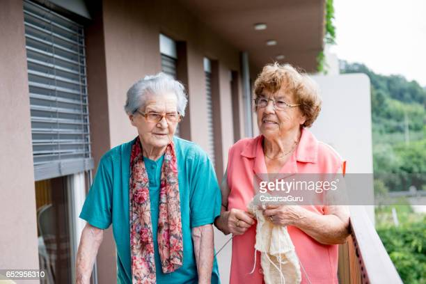 two seniors women socializing outdoors at the nursery home - residential care stock photos and pictures