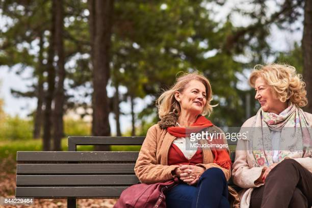 two senoir woman talking - friends stock photos and pictures
