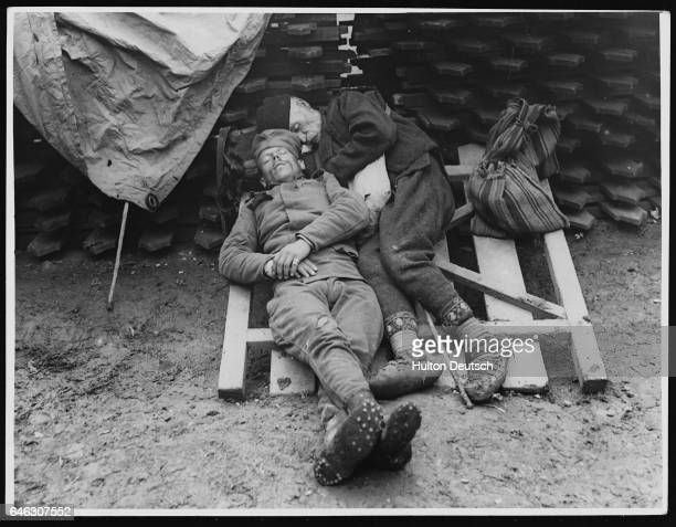Two Serbian soldiers one young one older sleep on a tilted gate it keeps them out of the mud having finished there duty in the trenches