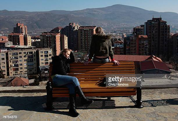 Two Serbian teenagers sit on a hill over the Serbian side of their city with the Albanian half in the distance February 14 2008 in Mitrovica Serbia...