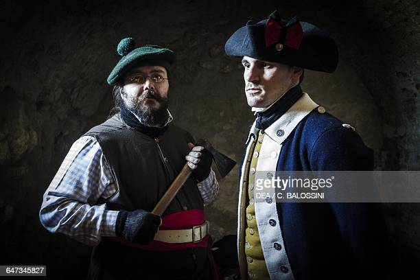 Two sergeants of the 4th Massachusetts Regiment one wearing a wool cap and holding an ax and the other wearing a tricorn hat and blue uniform...