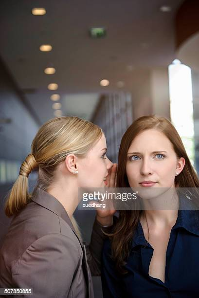 Two serious young businesswomen whispering in office
