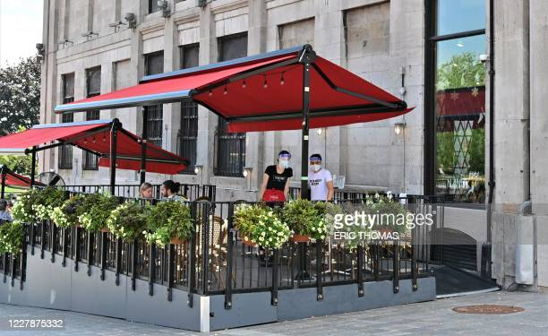 Two servers wait for clients in a restaurant terrace on the Place Jacques-Cartier, close to the Old-Port in central Montreal, Canada on July 28,...
