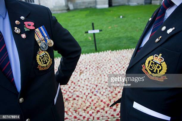 Two serving soldiers in civilian suits but wearing the insignia and badges of the Royal Military Police talk quietly together while poignantly paying...