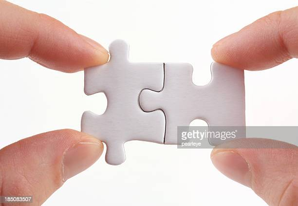 Two sets of fingers holding two puzzle pieces together