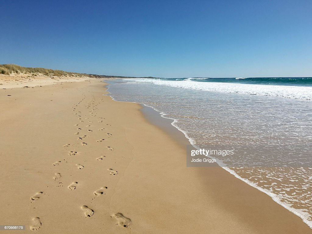Two sets of footprints together on secluded beach : Stock Photo