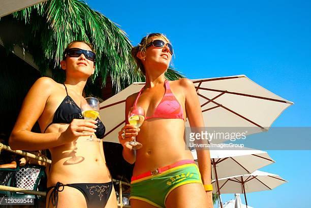 Two sexy women enjoying drinks at a beach bar Sa Trincha Las Salinas Ibiza 2006