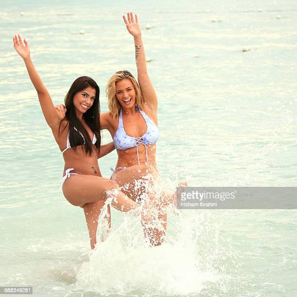 Two sexy women in bikini kicking water on beach