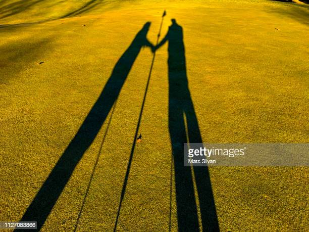 two shadow golfer handshake after finished golf tour on hole 18 with flag - golf tournament stock pictures, royalty-free photos & images