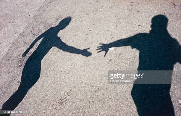 two shadows reaching out - shadow stock pictures, royalty-free photos & images