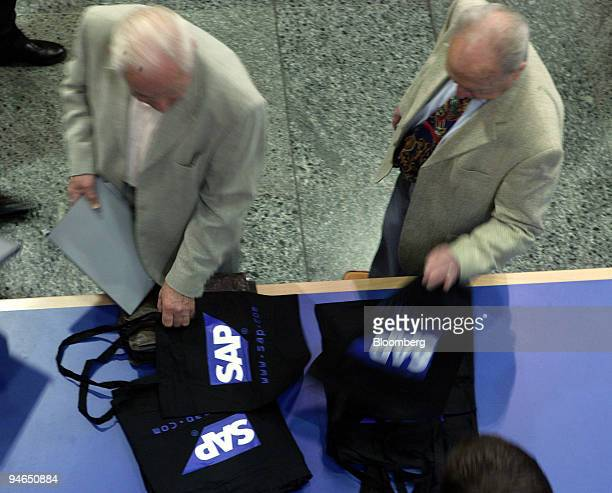 Two shareholders grab bags with the SAP AG logo during the company's annual meeting in Mannheim, Germany, Tuesday, May 9, 2006.