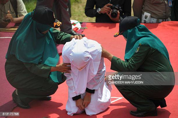 Two sharia policewomen help a woman after she received a caning for breaking Islamic law during a public punishment in Banda Aceh on March 1 2016 The...