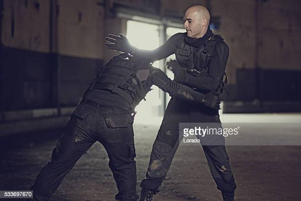 two shaven headed swat team members sparring in abandoned warehouse - martial arts stock pictures, royalty-free photos & images