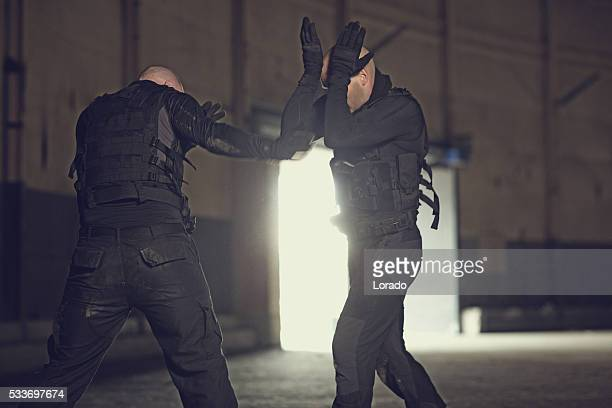 Two shaven headed swat team members sparring in abandoned warehouse