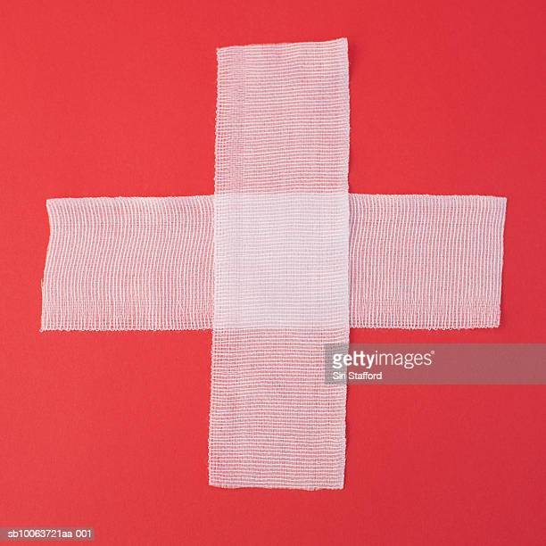Two sheets of gauze forming cross on red background, overhead view