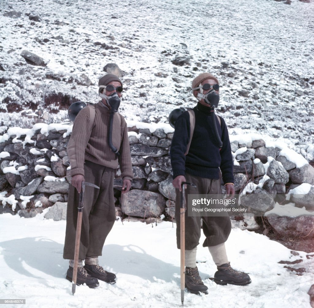 Two Sherpa porters wearing oxygen equipment and carrying ice-axes, Nepal, March 1953. Mount Everest Expedition 1953.