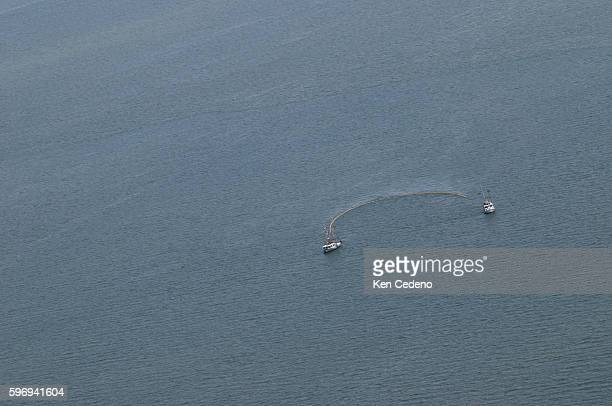 Two ships using booms circle and contains oil from the site of the BP Deepwater Horizon oil spill in the Gulf of Mexico Sunday July 11 2010 BP is...