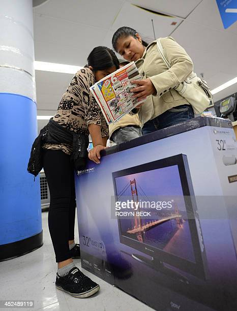 Two shoppers look at a sales circular at the Walmart in the Crenshaw district of Los Angeles on Black Friday November 29 2013 US stocks Friday moved...
