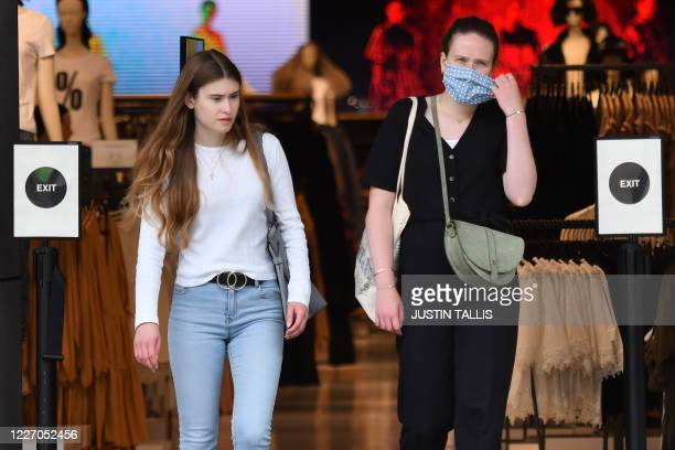 Two shoppers one taking off her protective face mask leave Reserved on Oxford Street in London on July 14 2020 Face masks will be compulsory in shops...