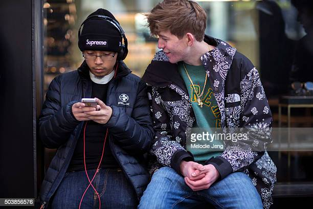 Two shoppers wait outside the Supreme store in Soho wear a black Supreme beanie Beats headphones a RLX puffer jacket Northface x Supreme paisley...