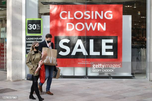 Two shoppers wearing masks because of the coronavirus pandemic walk past a closing down sale sign in the centre of Cardiff on October 23 hours before...