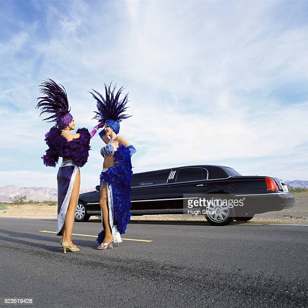 two show girls outside a limo on deserted road - hugh sitton stock-fotos und bilder