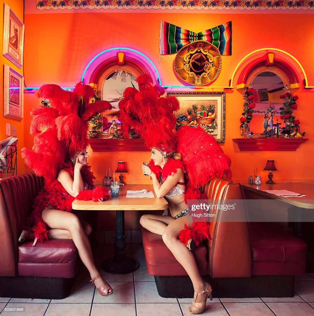 Two showgirls drinking cocktails in bar : Stock Photo