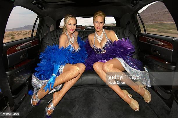 two showgirls in backseat of limo - hugh sitton stock-fotos und bilder