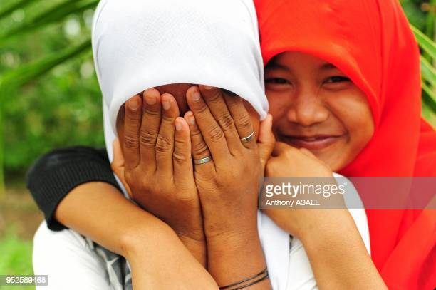two shy girl friends with veil and hiding in front of camera Banda Aceh Sumatra Indonesia