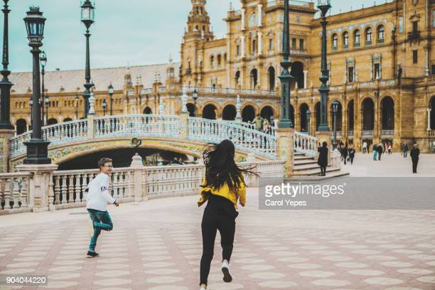 two sibling running across España square,Seville, Spain