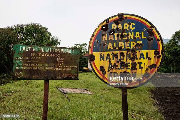 Two signs are posted at the entrance of the starting base for the walk to the top of Mount Nyiragongo Bullet holes on the right sign witness armed...