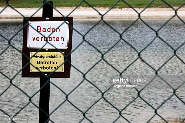 Two signs Baden verboten and Privatgrundstueck, Betreten verboten, German for Bathing prohibited and Private property, keep off, prohibition signs on the beach, wire mesh fence
