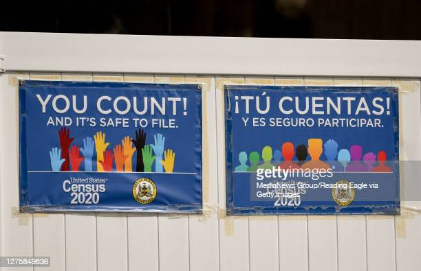 """Two signs, in English and Spanish, that read """"You Count! And it's safe to file. Census 2020"""" for the 2020 Census on a fence along 13th street in..."""