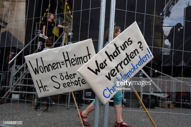 Two signs saying 'Wohnen = Heimat / Hr. Soeder, Seehofer' - 'Living is community / home' and 'Wer hat uns verraten? / Christdemokraten' - 'Who...