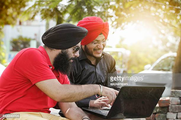 Two Sikh men using laptop